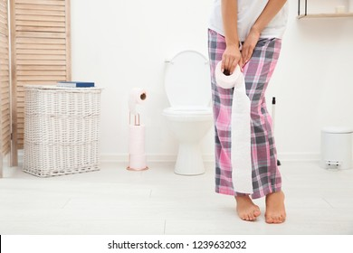 Young woman standing with urine urgency and toilet paper in bathroom