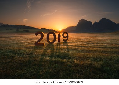 Young woman standing and watching the rising sun, uncertainty for upcoming 2019 new year. Future and time passing concept.