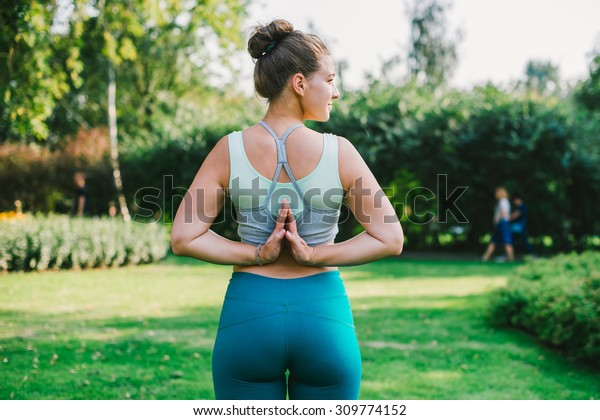 Young woman stands in back namaste yoga pose. Freedom concept. Calmness and relax, woman happiness
