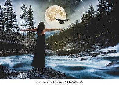 Young woman stands by the river at full moon