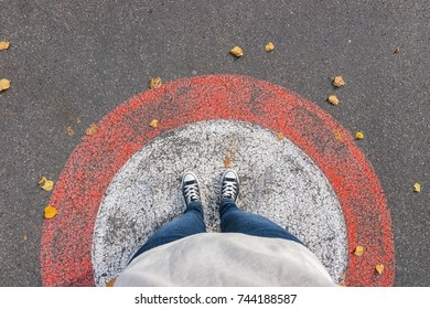 Young woman stands in a circle at autumn on the streets, personal pespective from above.