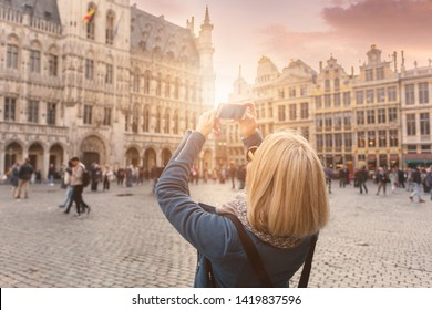 A young woman stands with her back to the camera and takes pictures on her phone for social networks against the background of the Grand Place in Brussels, Belgium