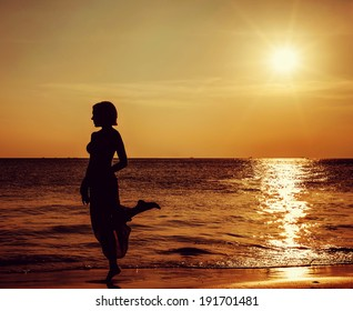 young woman stands on the beach during a beautiful sunset
