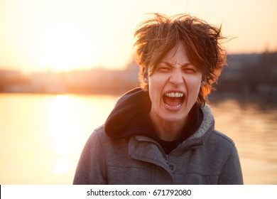 A young woman stands on a city street with a hairy hairdo and screams in hysterics against the backdrop of the rising sun.
