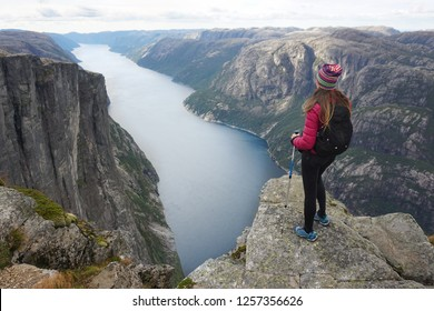 Young woman stands on the edge of a cliff near Kjerag in Norway, above the fjord. Hiking in Rogaland