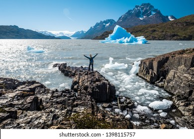 Young woman stands on the rocky coast of the Grey Lake with raised hands and enjoys the blue iceberg view. Torres del Paine National Park, Chile