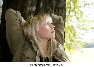 young woman stands on a tree