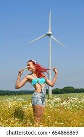 A young woman stands  in a wheat field with a wind  turbine behind her. Smilingly she shows off her  appreciation for this type of alternative energy.