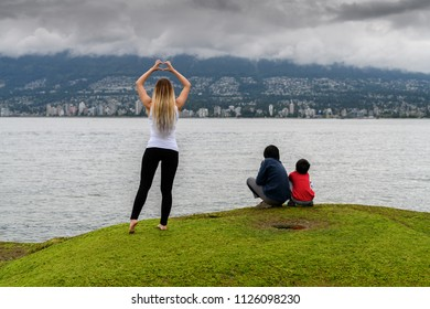 Young woman in the Stanley Park forming heart shape with her hands and showing it toward Vancouver, British Columbia.