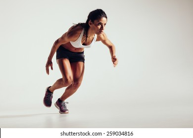 Young woman starting to run and accelerating over grey background. Powerful young female athlete running in competition.