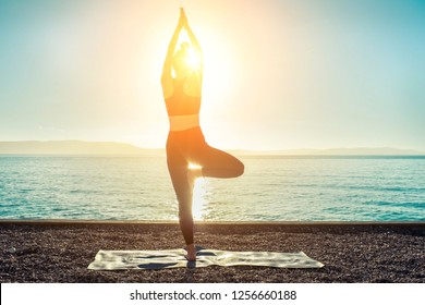 Young woman stay in Yoga pose on the sea coastline under sun light at morming time. Summer fresh air from sea.