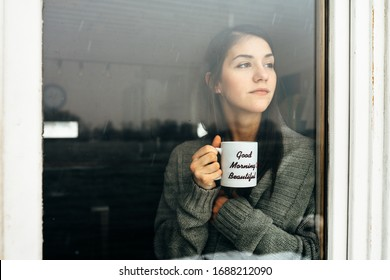 Young woman staying at home drinking coffee/tea,looking trough the window.Starting the day,morning ritual.Quaratine self isolation concept.Worried woman indoors activity.Mental challenge.Bad mood