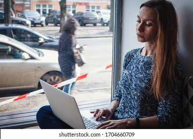 Young woman staying on quarantine at home and work remotely