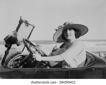 Young woman at steering wheel of automobile. 1921.
