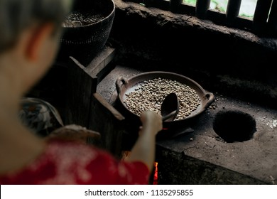 Young woman stirring coffee beans while roasting