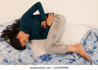 Young woman with stomach ache suffering isolated over white background .