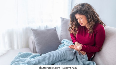Young woman with stomachache holding and taking medicine pill, health care. Millennial ill sick woman taking painkiller medicine to relieve stomachache pain sit on bed in the morning