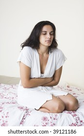 Young woman with stomachache sitting on her bed