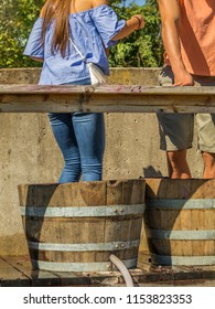 Young woman  stomping grapes in wooden barrel during the  Grape Stomp Festival; Missouri, Midwest