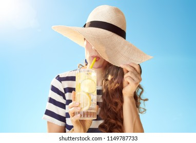 young woman in straw hat against blue sky hiding behind straw hat and drinking refreshing cocktail