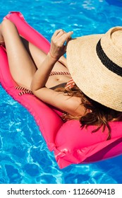 young woman in straw hat and bikini  floating on inflatable mattress at swimming pool