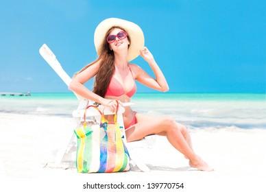 young woman in straw hat and bikini sitting on beach chair