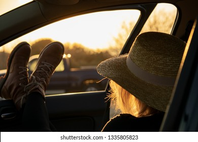 Young woman with straw hat chilling in car at sunset. Road trip concept