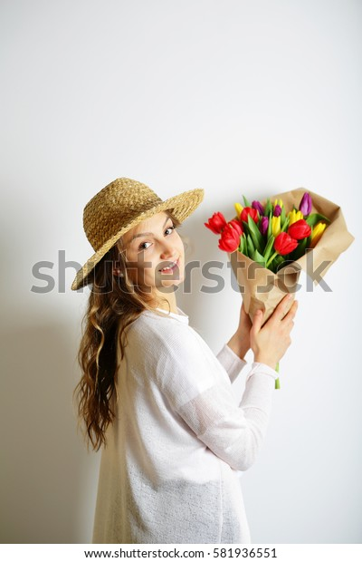 Young woman in a straw hat holding a bouquet of colorful spring flowers. Concept March 8
