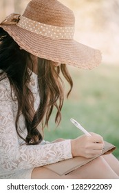 young woman in a straw hat with long hair sits on the shore of the lake on the grass and writes a letter. concept of romance