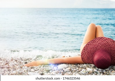 Young woman in straw hat lying sunbathe on a tropical beach,  relax on  vacation