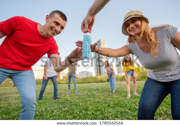 a young woman with a straw hat, and a young man, playing capture the flag in the meadow , whoever wins takes the protective mask, field games, new normal and new sociality