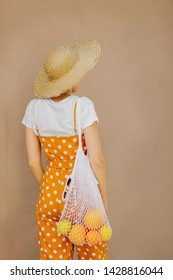 Young woman in straw hat with a mesh bag of fruit. Sustainable lifestyle. Plastic free concept.