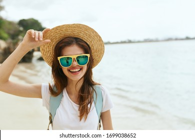 young woman in a straw hat on the ocean