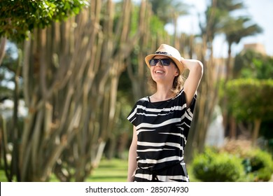 Young woman in straw hat, sunglasses and summer dress walking beside giant cactus on southern sunny street in green oasis, looking around her with excited expression
