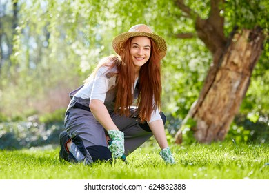 Young woman with straw hat working in the garden