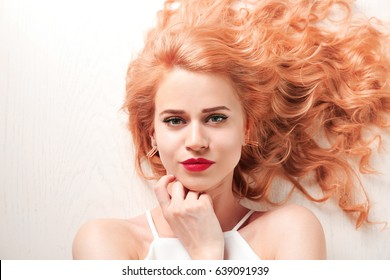 Young woman with strawberry blonde hair on wooden background