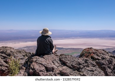 Young woman in a stray hat sitting on a cliff overlooking Alvord Desert. Steens Mountains, south Oregon