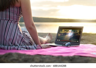 Young woman streaming a movie with laptop computer on beach at sunset. Watching film stream on imaginary online service outdoors. Video player on screen.