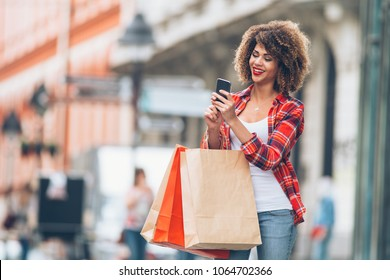 Young woman at the street with shopping bags using mobile phone