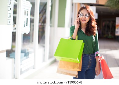 Young woman at the street with shopping bags talking on mobile phone