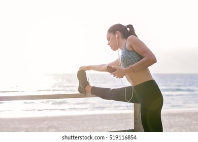 Young woman stretches her leg up on a park bench. She has sweat and is wearing sports clothing. The beach and ocean are in the background. Washed out exposure creating copy space.