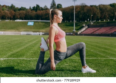 Young woman stretches on the stadium before a workout