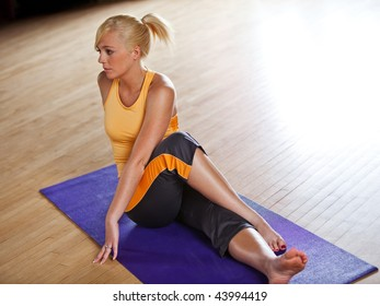 A young woman stretches on a yoga mat. A large white area in the upper right is perfectly suited for text.