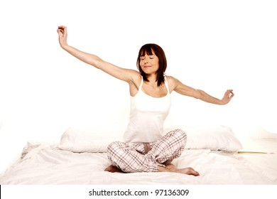 A young woman stretches as she wakes up from a good nights sleep. Waking up.