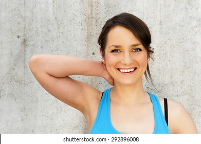 young woman stretching after run by the wall in city with big smile. in blue sportswear.