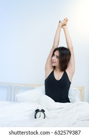 young woman stretching in bed after wake up, entering a day happy and relaxed after good night sleep.