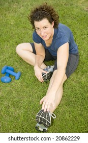 Young woman stretching before exercising with dumbells on a lawn.