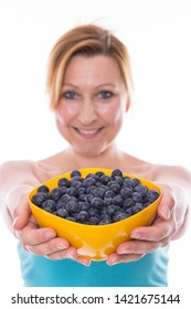 Young woman is stretching a bowl of blueberries into the camera