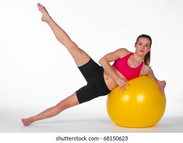 young woman stretching exercise with yellow pilates ball