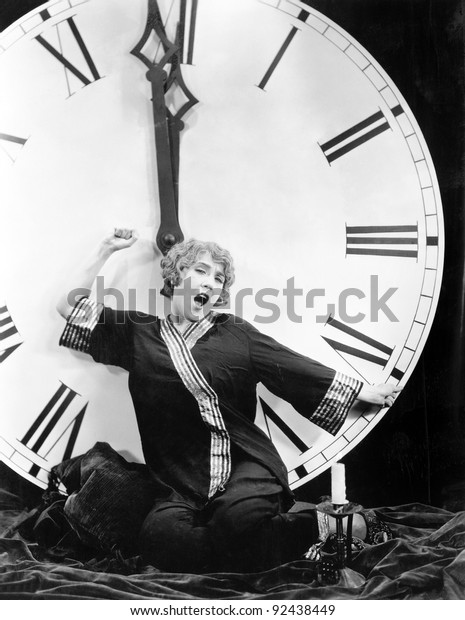 A young woman stretching in front of a giant clock striking midnight